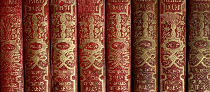 Volumes of All the Year Round, bound in red leather, on a shelf